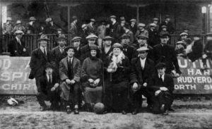 Photograph of Margaret Carlson (centre) at a football ground