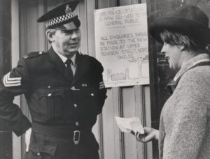 Photograph of a policeman directing a member of the public to the new police station, January 1976