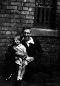 Photograph of Annabel with her uncle, George Gray. This was taken in the backyard at Maude Terrace in about 1936/37.  The pantry window is in the background.