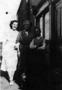 Annabel Graham with her Grandmother Martha Gray (nee Cowan) and younger brother William, outside the shop at Old Allotment. This photograph was taken before 1953. The shop was next to the Northumberland Arms, but across a little street.